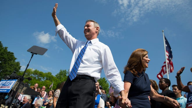 Former Maryland governor Martin O'Malley waves as he arrives with his wife, Katie O'Malley, to his campaign announcement event on May 30, 2015, in Baltimore.