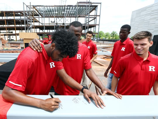 Rutgers basketball player Myles Johnson signs the final piece of structural steel at the Ôtopping off ceremonyÕ at the 307,000 square foot Rutgers RWJBarnabas Health Athletic Performance Center. June 3, 2018. Piscataway, NJ