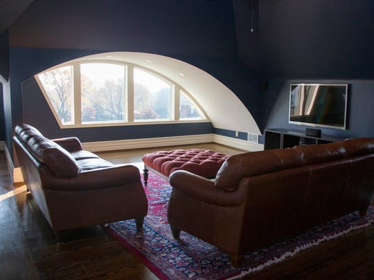 The soaring ceiling follows the roof line and a crescent-moon window cuts through the roof to make this former attic into a third-floor movie lounge with a view of Lake St. Clair.