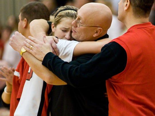 In this 2009 photo, Kelsee Rehm hugs coach Greg Moore
