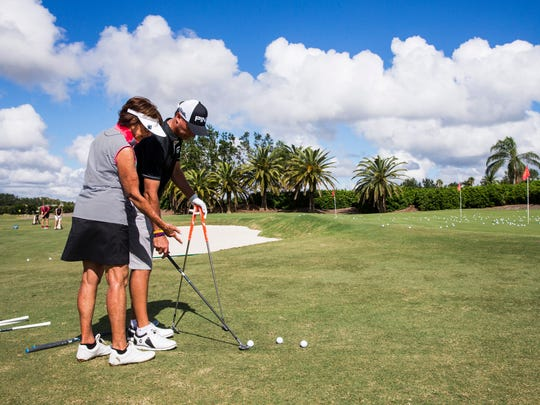 "Former PGA Tour player Chris DiMarco helps a woman with her chipping technique during a clinic before the ""Battle of the Sexes"" fundraiser for Swinging with a Purpose on Monday Nov. 6, 2017 at Quail West Golf and Country Club in Bonita Springs."