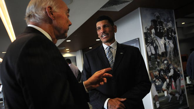 New Wolf Pack head football coach Jay Norvell gets congratulated by university president Marc Johnson following a press conference Friday at Mackay Stadium.