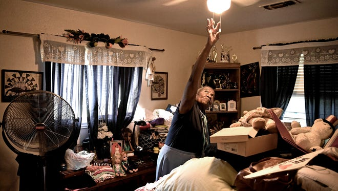 With one fan already running in this bedroom, Helen Benjamin reaches to turn on the ceiling fan after opening the windows to let her house air out after flooding caused by Hurricane Harvey in Houston.