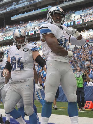 Theo Riddick and Travis Swanson celebrate after a touchdown on Sunday.