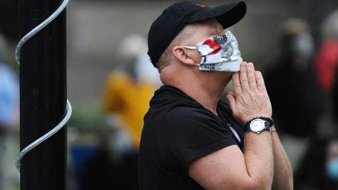 Sean Moroney, of Sagamore Beach, closes his eyes as he listens to the music played at the end of Monday's interfaith service on the Hyannis Village Green. To see more photos, go to capecodtimes.com/photos.