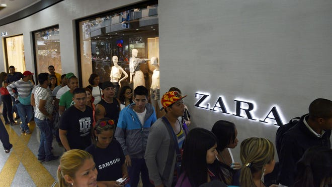 People line up to enter the Spanish clothes chain Zara store in Caracas on June 18, 2014.