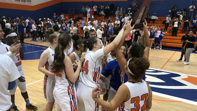 The Cape Coral girls basketball team celebrates winning the District 7A-10 title over Charlotte High on Friday, Feb. 9.