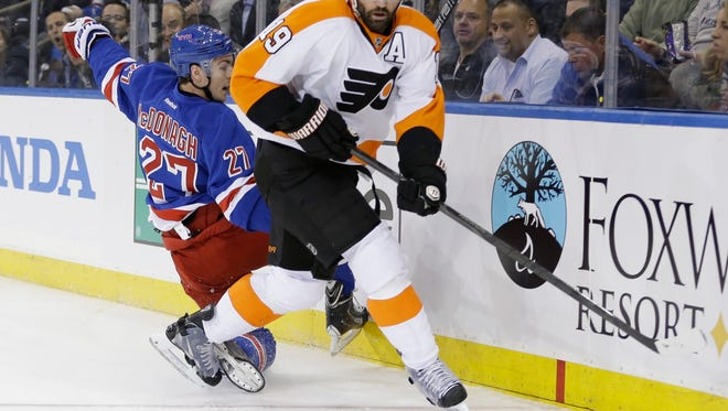 The Philadelphia Flyers' Scott Hartnell, right, looks to pass after taking the puck from Rangers defenseman Ryan McDonagh, left, in the first period.