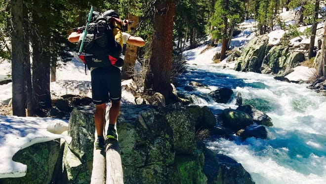 In this Friday, June 16, 2017, photo, Jake Gustafson crosses Bear Creek along the Pacific Crest Trail near Kings Canyon National Park, Calif.
