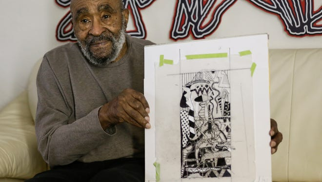 """Charles McGee of Detroit, 92, poses for a photo with the sketch of his upcoming mural """"Unity"""" at his home in Detroit, May 9, 2017. The 100-foot tall mural will be painted on the north-facing wall of 28 Grand Microloft building in downtown Detroit."""