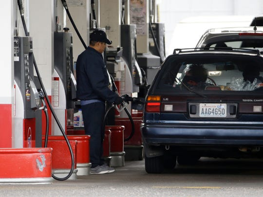 In this May 6, 2015, file photo, cars line up as an attendant pumps gas at a station in Portland, Oregon.