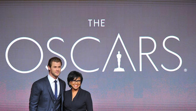 Chris Hemsworth, left, and President of the Academy Cheryl Boone Isaacs pose at the 86th Academy Awards nomination ceremony on Thursday, Jan. 16, 2014 in Beverly Hills, Calif. The 86th Annual Academy Awards will take place on Sunday, March 2, at the Dolby Theatre in Los Angeles.