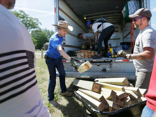 Veterans and volunteers unload supplies at the Beland Manning Park, Monday, June 27, 2016, in Detroit. Hundreds of veterans are in the financially troubled city for a week to rebuild areas that have been neglected by poverty, crime and a lack of resources. It's the latest and largest effort undertaken by St. Louis-based The Mission Continues, which encourages and aids volunteerism by disabled and wounded veterans. (AP Photo/Carlos Osorio)