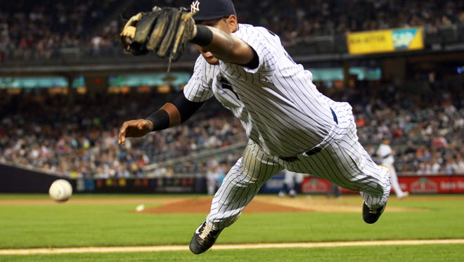 New York Yankees third baseman Yangervis Solarte dives but cannot catch a pop foul bunt against the Seattle Mariners at Yankee Stadium.
