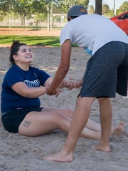 Michelle Lujan gets a hand-up out of the sand by Javier Ortega during a pickup sand volleyball game on a Sunday evening in June at Meerscheidt Recreation Center.