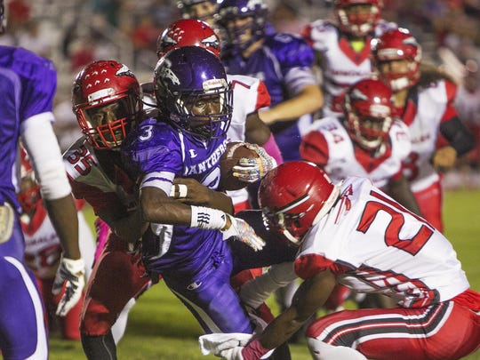 Cypress Lake's Eddie Teague, center, is double-teamed by Immokalee's Roney Paul and Tharique Toussaint as the Immokalee Indians visit the Cypress Lake Panthers Friday in Fort Myers.