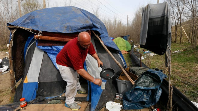 Lial Boggess pours water he boiled on a skillet into a plastic cup to make instant coffee Wednesday, March 30, 2016, at his tent in a homeless camp off SW 14th Street in Des Moines. Boggess said he thinks the tiny-home village concept could work, as long as trash and water services are available to them.