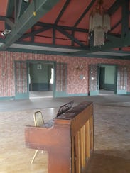 An out-of-tune piano sits in the dusty ballroom of
