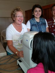 Kathy uses an autorefractor to get a young Nicaragua