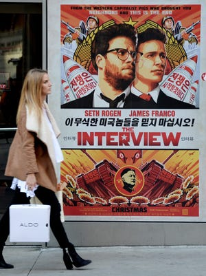 A woman walks past a poster for the film 'The Interview' outside a theater in New York on Dec.18.