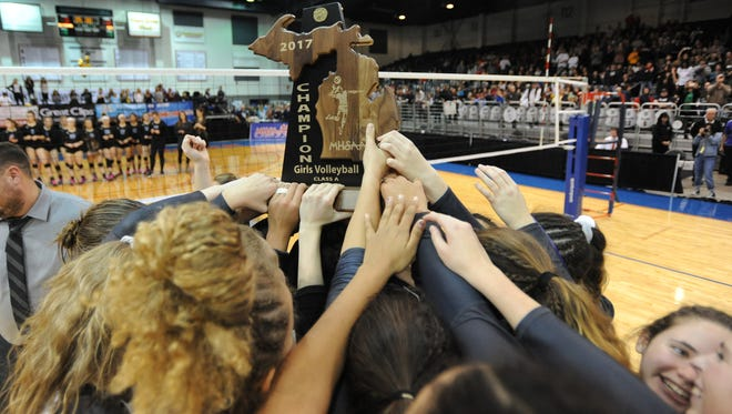 The Novi High volleyball team members hold up their trophy after winning the Class A state title in straight sets over Bloomfield Hills Marian Saturday.
