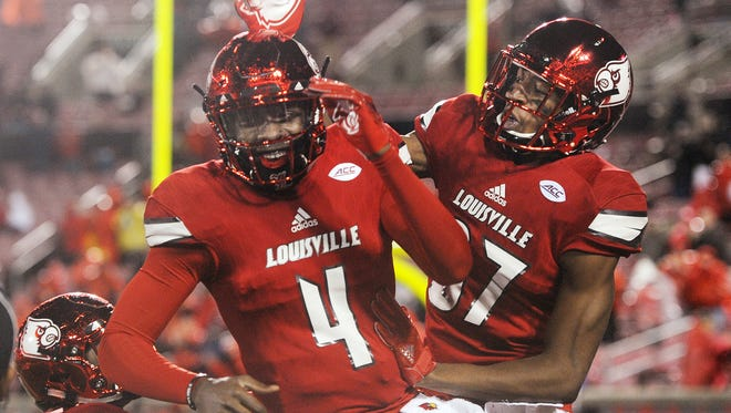 Louisville's Dez Fitzpatrick (right) congratulates Louisville quarterback Jawon Pass (4) after Pass through Fitzpatrick a touchdown pass against Syracuse on Saturday at Papa John's Cardinal Stadium. Nov. 18, 2017