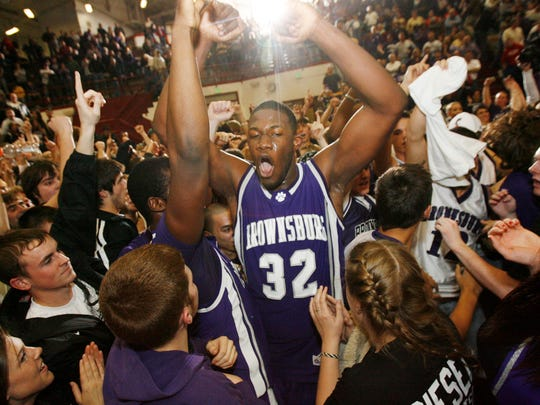 Brownsburg's Julian Mavunga (32) is surrounded by teammates and fans as they celebrate Brownsburg's 63-59 victory over Carmel at the ISHAA Class 4A Regional Championship game at Southport High School, Saturday  March 8.  (Joe Vitti/Indianapolis Star)