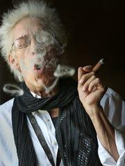 Bill Levin blows smoke rings as he smokes a cigar at