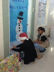 Vanessa Castro and Anabella Gutierrez decorated a door.