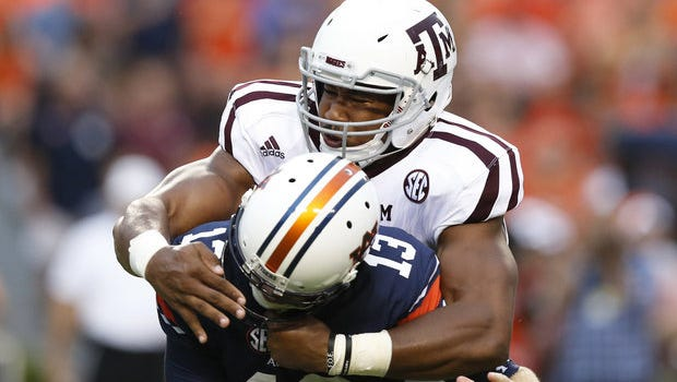 Texas A&M defensive lineman Myles Garrett, top, sacks Auburn quarterback Sean White in the first half of an NCAA college football game, Saturday, Sept. 17, 2016, in Auburn, Ala