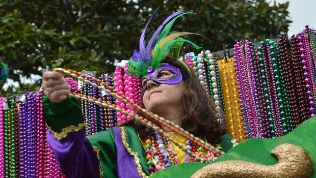 A krewe rider throws beads during the 2014 Alexandria Mardi Gras Parade.