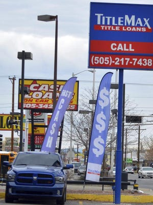 In this Jan. 13, 2017 photo, store signs for payday loan companies sit along a busy street in Albuquerque, N.M. Two state lawmakers are taking aim at the payday loan industry in New Mexico once again, seeking to limit exorbitant interest rates often charged by lenders.