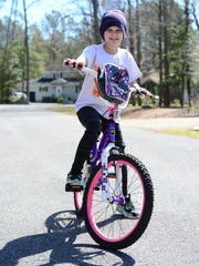 Brianna Meritt, 9, takes a stroll around the block on her bike in Ocean Pines on Monday, March 20, 2017.