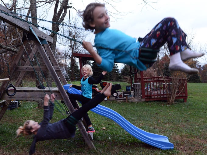 Skylar and Logan play with their neighbor on the swing set.