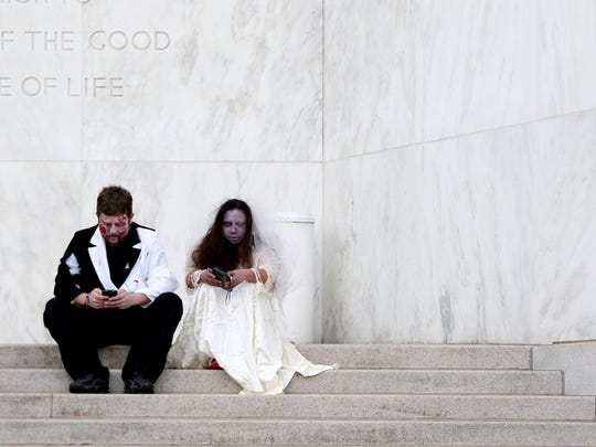 Travs Boles and Elizabeth Voetberg sit on the steps of the State Capitol during a Zombie Walk in Salem on Oct. 24.