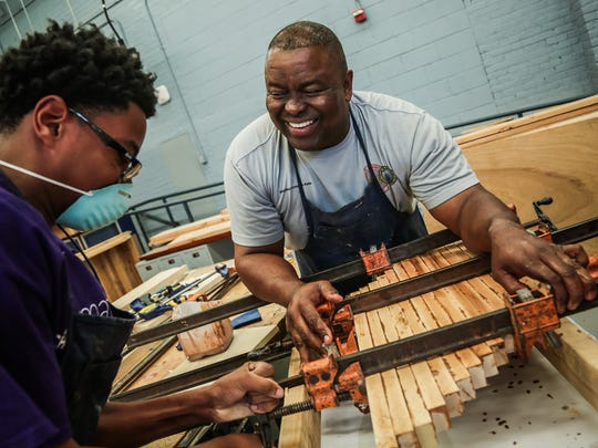 In Chicago, Michael Gaston, left, 16, learns the art of woodworking during a jobs program. He's with teacher Arrington Fultz, 56, of Chicago during the After School Matters wood shop program at Chicago Vocational Career Academy on Thursday, July 21, 2016.