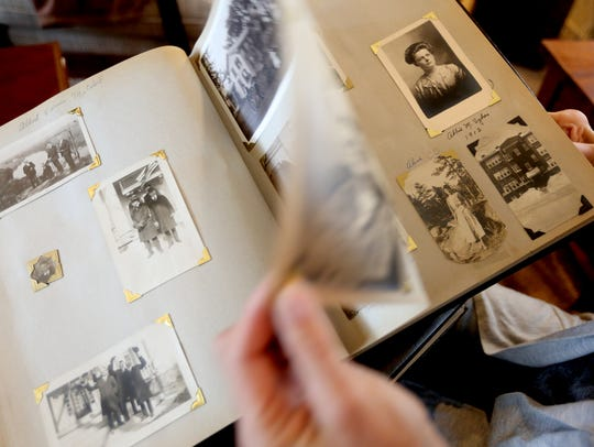Val Springer looks through photo albums, dating from