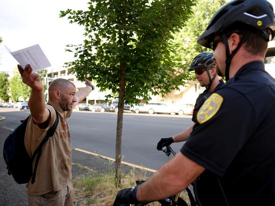 Salem Police Officers Andrew McFerron, right, and David Smith talk with a man experiencing homelessness in downtown Salem on Tuesday, May 29, 2018.