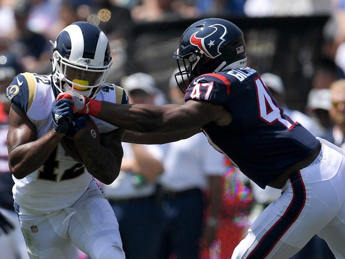 Los Angeles Rams running back John Kelly runs around Houston Texans linebacker Kennan Gilchrist during the first half in an NFL preseason football game Saturday, Aug. 25, 2018, in Los Angeles. (AP Photo/Mark J. Terrill)