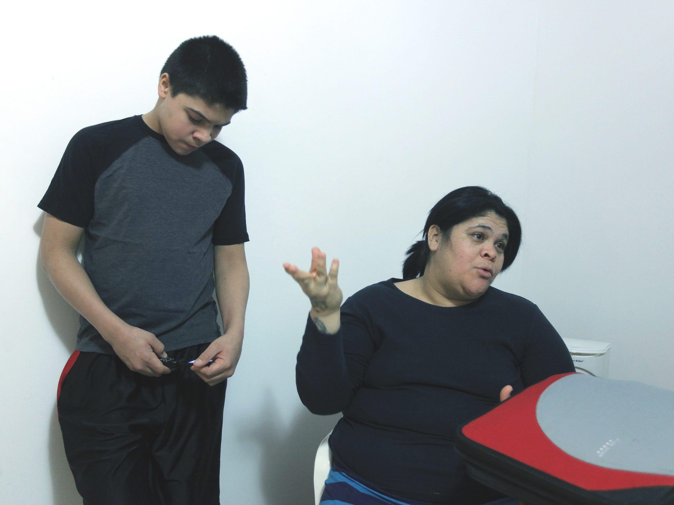 Juan Carlos Collado, 14, next to his mother, Yamitza