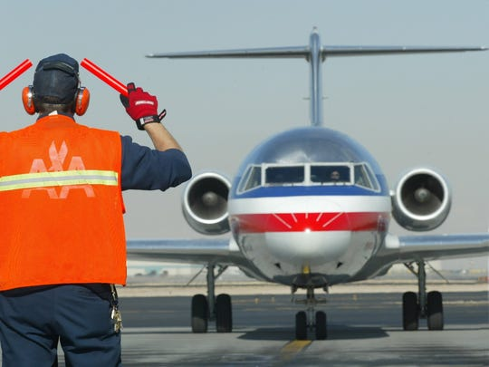 An American Airlines ramp employee guides a jet into