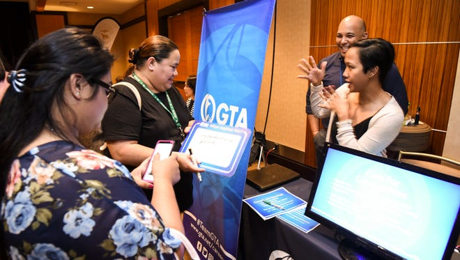 Restine Hernandez, front right, GTA learning and development manager, chats with job seekers visiting their table during the Guam Chamber of Commerce's Chamber Business Women Network 3rd annual Job Fair at the Westin Resort Guam in Tumon on Thursday, Feb. 1, 2018.