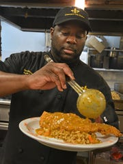 Crescent City Bistro owner Chef Darrell Johnson puts the finishing touches on one of his creations.