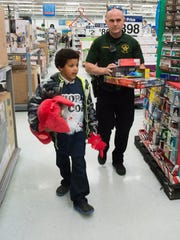 "Escambia County Sheriff's Deputy, Coy McKenna and Javen Morgan, shop for Christmas gifts at Wal Mart on Hwy. 29 during the law enforcement agency's annual ""Shop with a Cop"" event Friday afternoon."