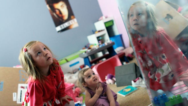 With her face reflected in a mirror, Coy Mathis, left, a transgender girl, plays with her sister, Auri, 2, center, at their home in Fountain, Colo.