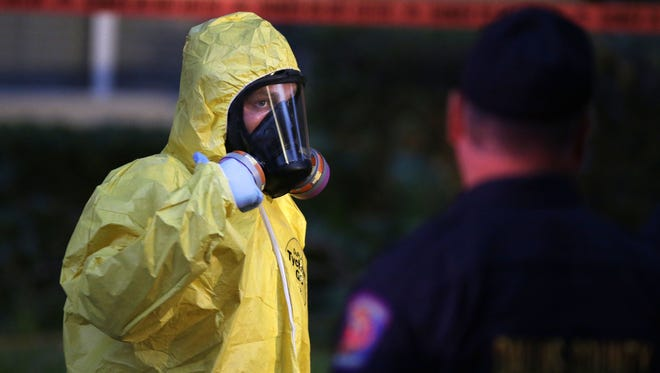 A hazmat worker looks up while finishing up cleaning outside an apartment building of a hospital worker, Sunday, Oct. 12, 2014, in Dallas. The Texas health care worker, who was in full protective gear when they provided hospital care for Ebola patient Thomas Eric Duncan, who later died, has tested positive for the virus and is in stable condition, health officials said Sunday.