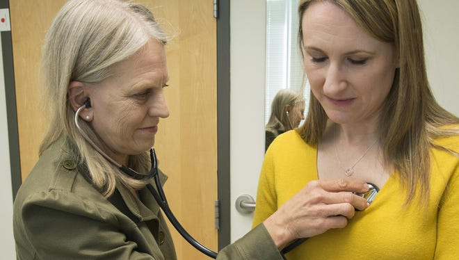In this 2016 photo provided by the University of Washington, Dr. Linda Vorvick examines Heather VanDusen at the UW Medicine Neighborhood Smokey Point clinic in Arlington, Wash. When emergency tests showed the telltale right-sided pain in VanDusen's abdomen was appendicitis, she figured she'd be quickly wheeled into surgery. But doctors offered her the option of antibiotics instead.