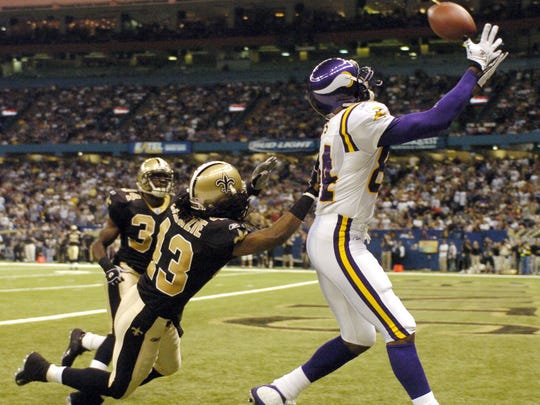 Vikings wide receiver Randy Moss (84) catches a touchdown pass over Mike McKenzie during Minnesota's 38-31 win over New Orleans in 2004.