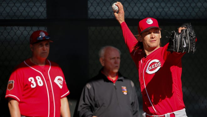 Cincinnati Reds pitcher Bronson Arroyo (61) throws in a bullpen session as manager Cincinnati Reds manager Bryan Price (38) and executive advisor to the CEO Walt Jocketty look on during Cincinnati Reds spring training, Wednesday, Feb. 15, 2017, at the Cincinnati Reds player development complex in Goodyear, Arizona.