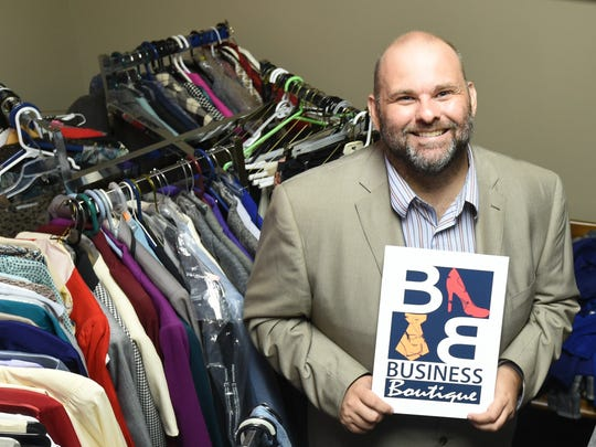 Arkansas State University-Mountain Home business instructor Johnny Howard shows off a logo a student made for  the Business Boutique. The Business Boutique has free professional clothes, which students can use for job interviews.